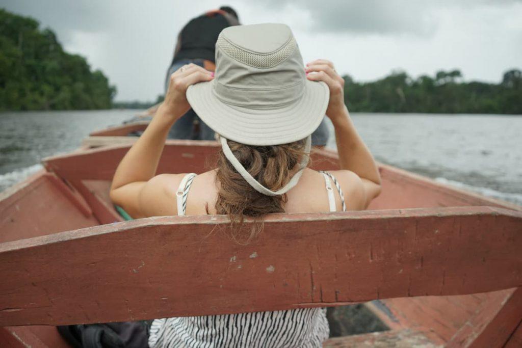 vrouw met hoed op de suriname rivier